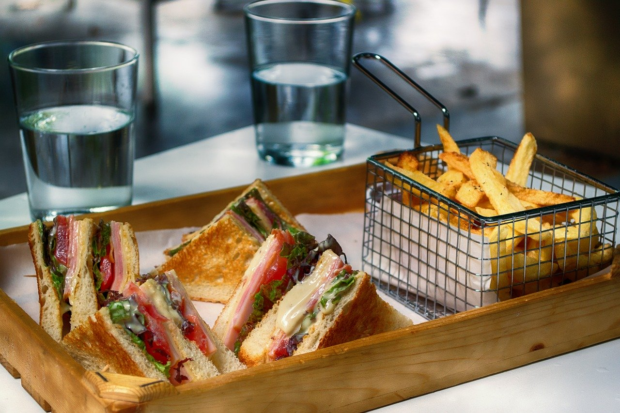 Fast food tray with club sandwich and French fries.