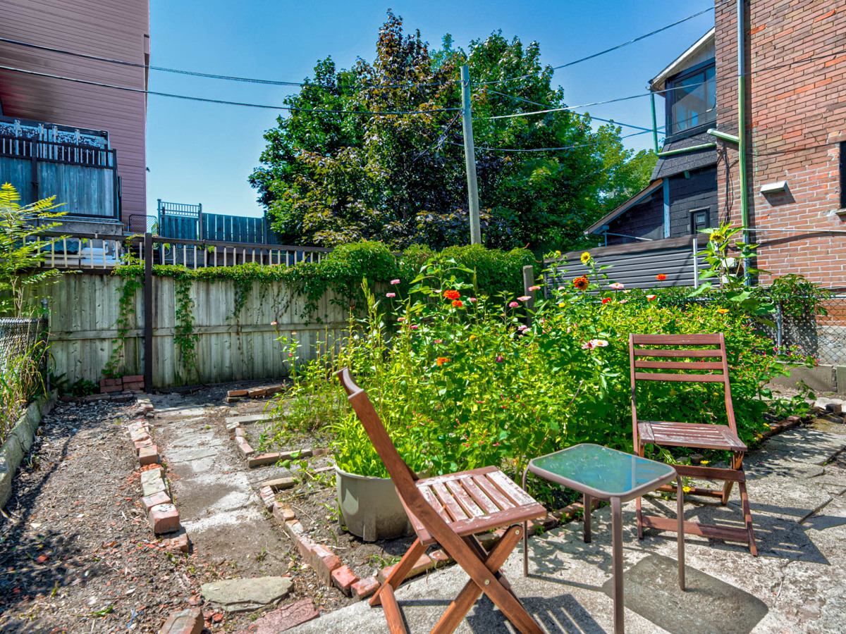 Small fenced garden with flowers and patio furniture.