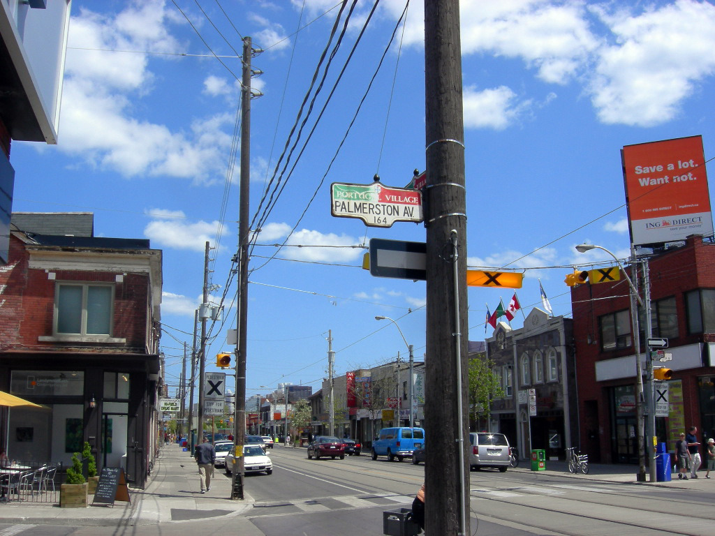 Street signs, pedestrians and cars along Little Portugal, Toronto.