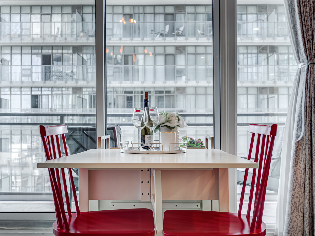 White dining table with wine on tray and 2 red chairs.