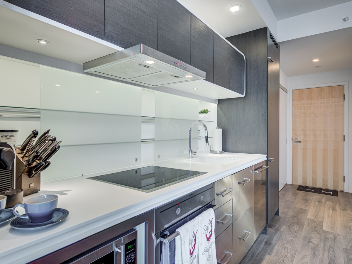 Condo kitchen with stainless steel appliances, dark wood cabinets and dull metal cabinets.