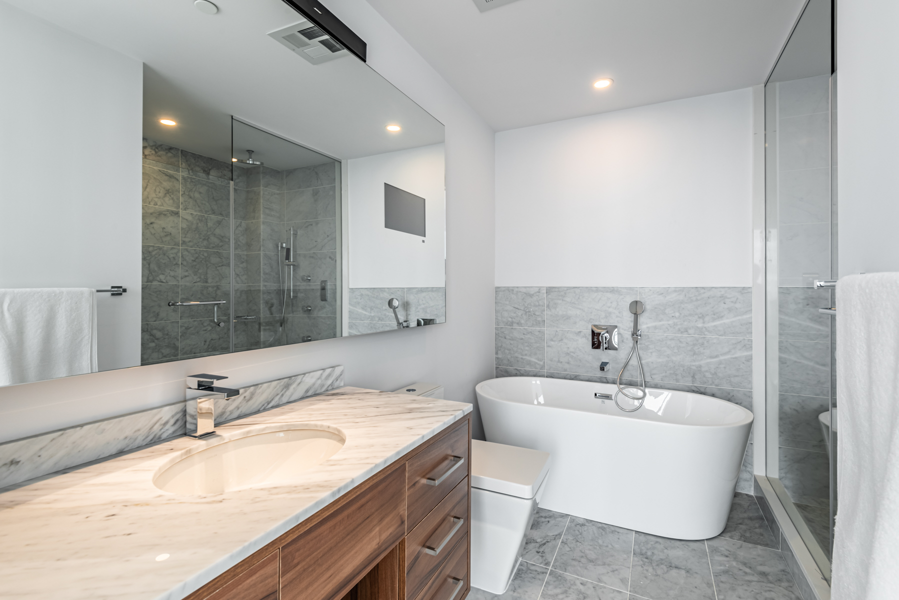488 University Ave #3102 master bath with marble tiles, granite counters, long mirror and big tub.