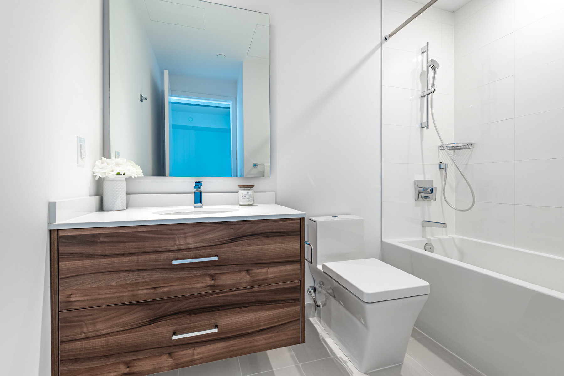 488 University Ave Unit 3102 4-piece bath with gray tiles and dark brown drawers.
