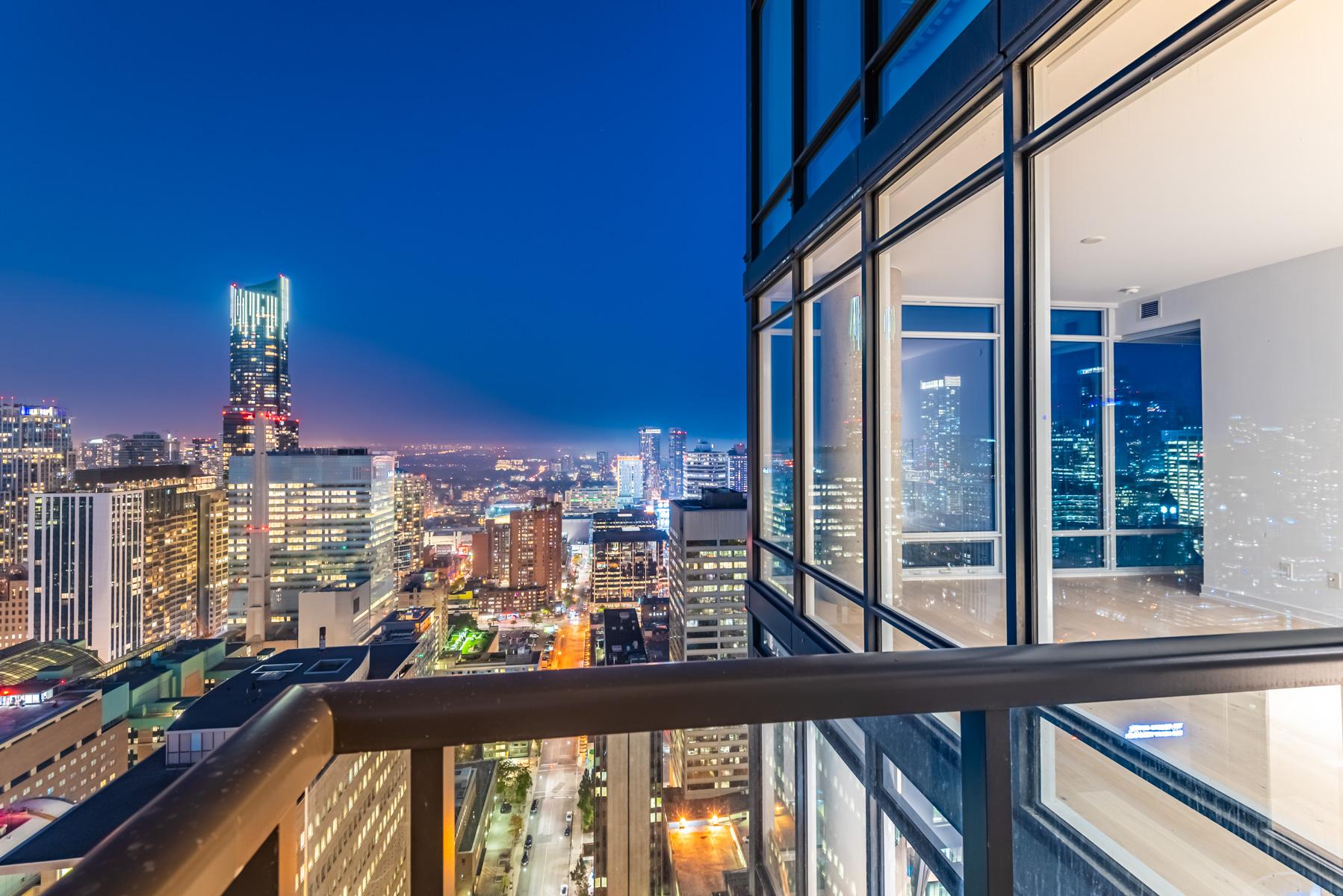 Night view of brightly lit Toronto skyline from 488 University Ave balcony.