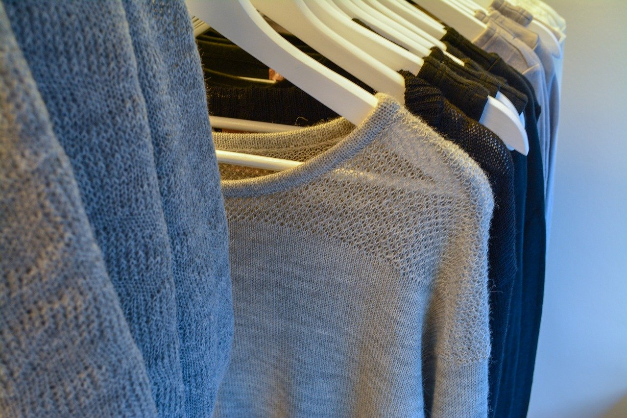 Close up of clothes rack with sweaters.