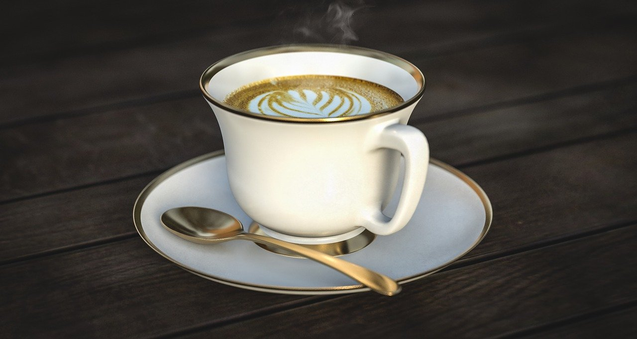 White cup and saucer with steaming coffee.
