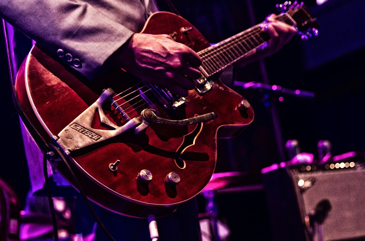 Close up of man holding red guitar.