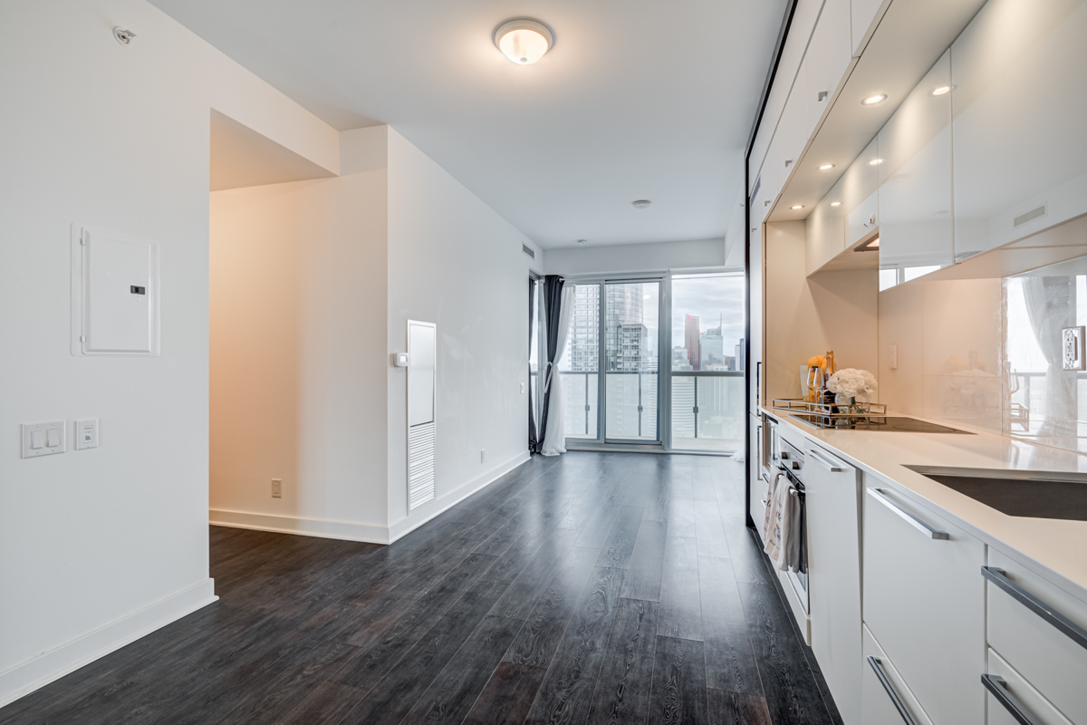 Empty condo with dark laminate floors, white kitchen and large windows.