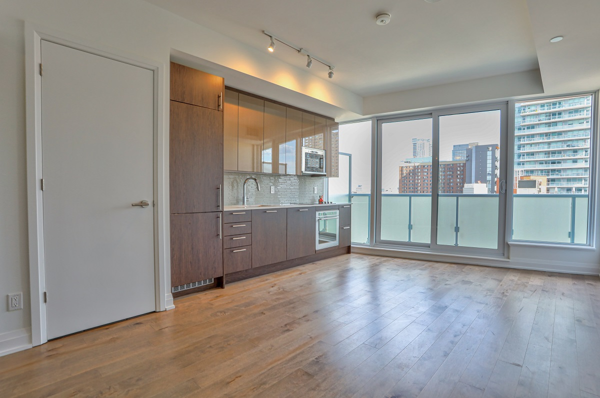 Empty condo with hardwood floors and large windows.