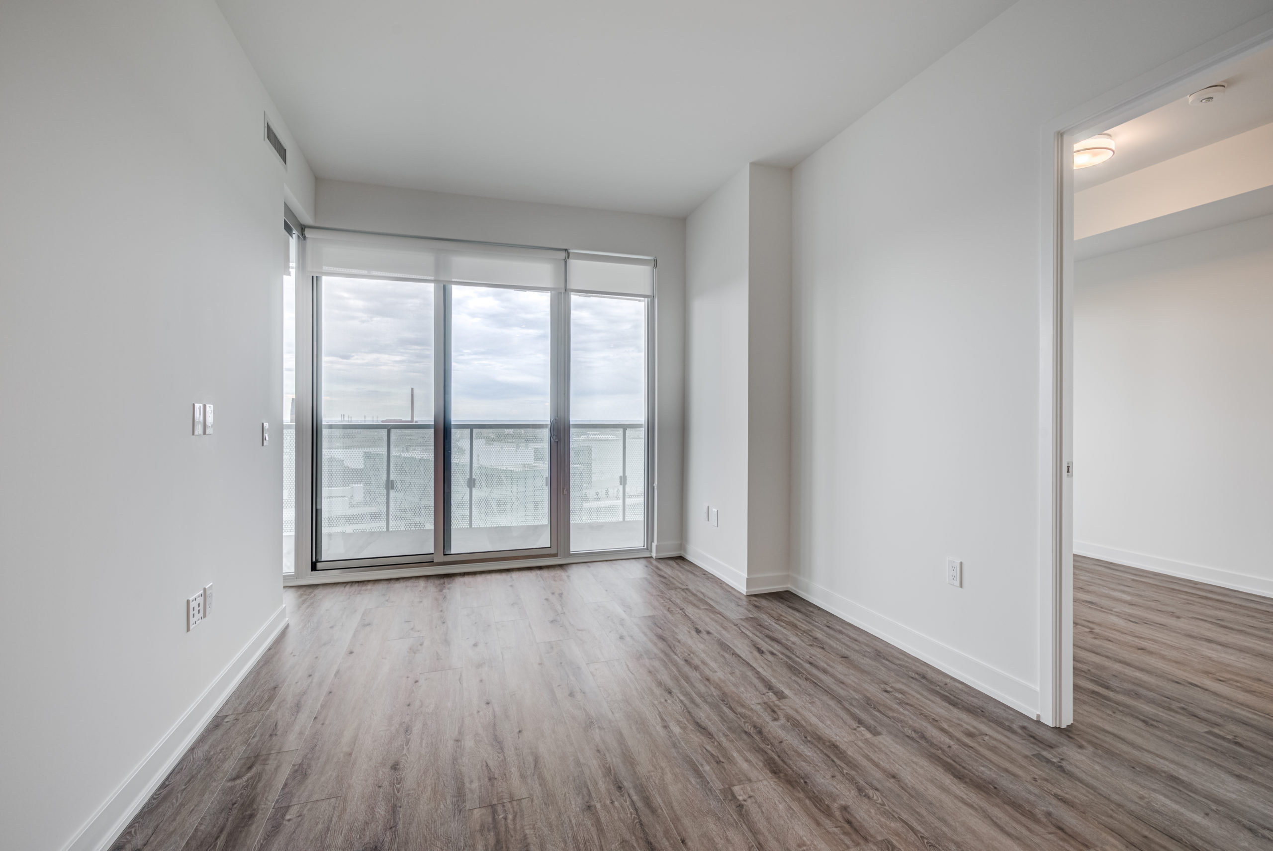 Brightly lit condo living room and walkout balcony.