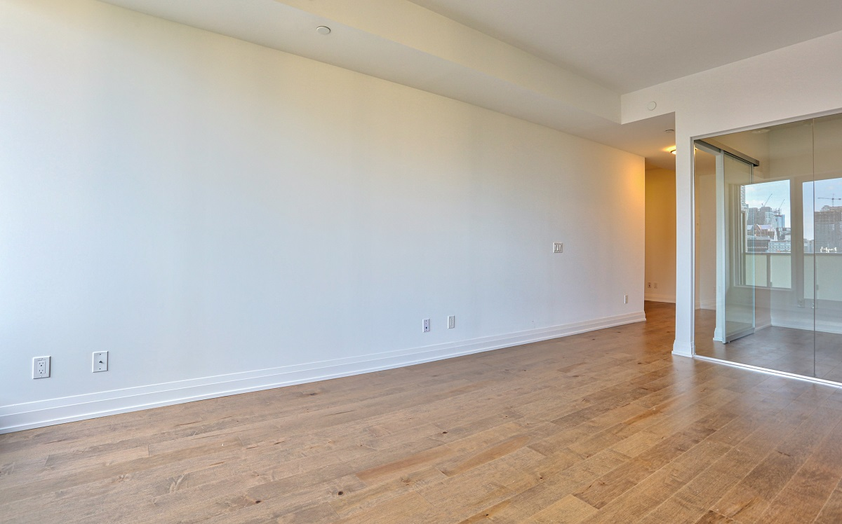 Brightly lit empty condo with hardwood floors.