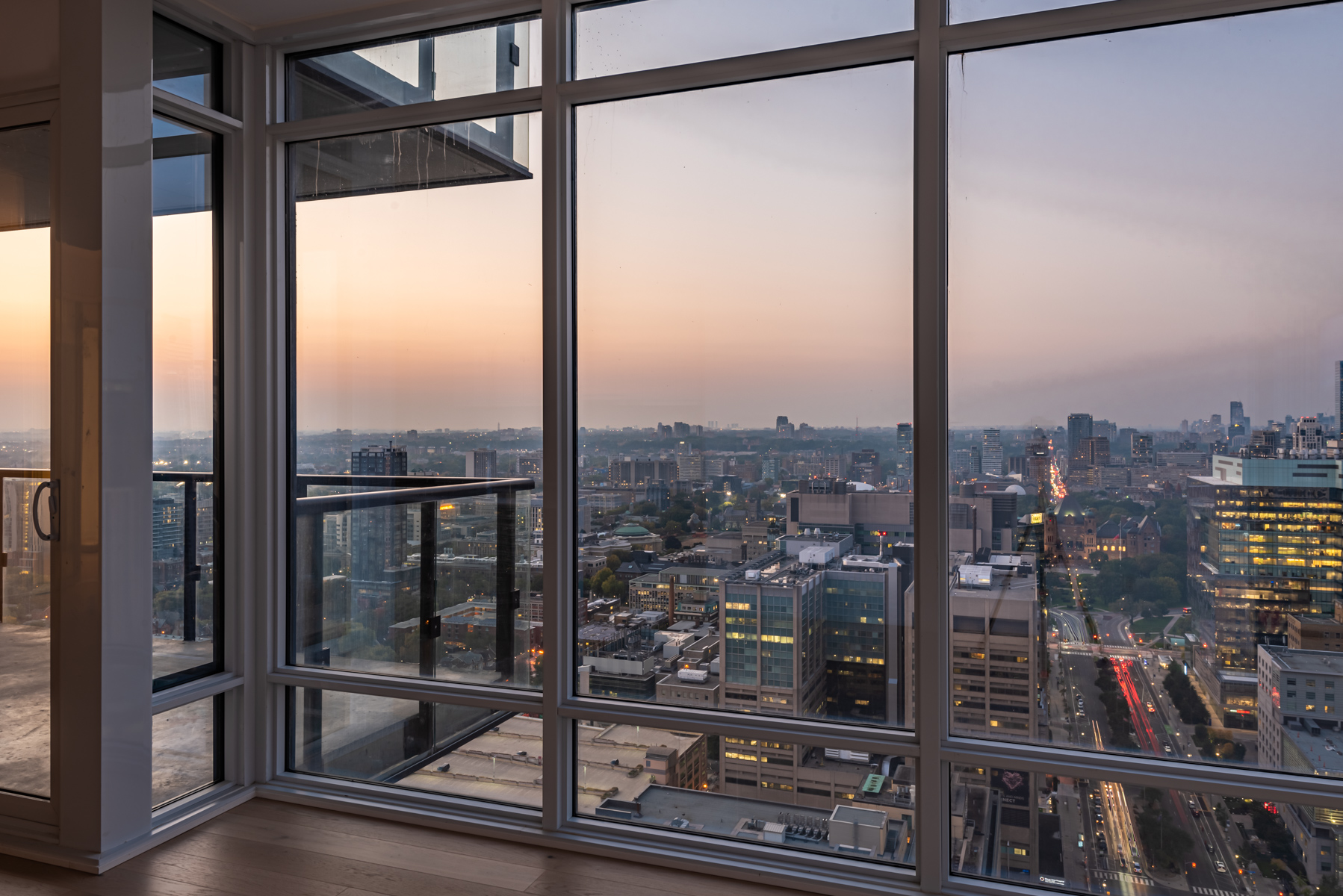View of Toronto from living room of 488 University Ave showing pinkish sky and city lights.