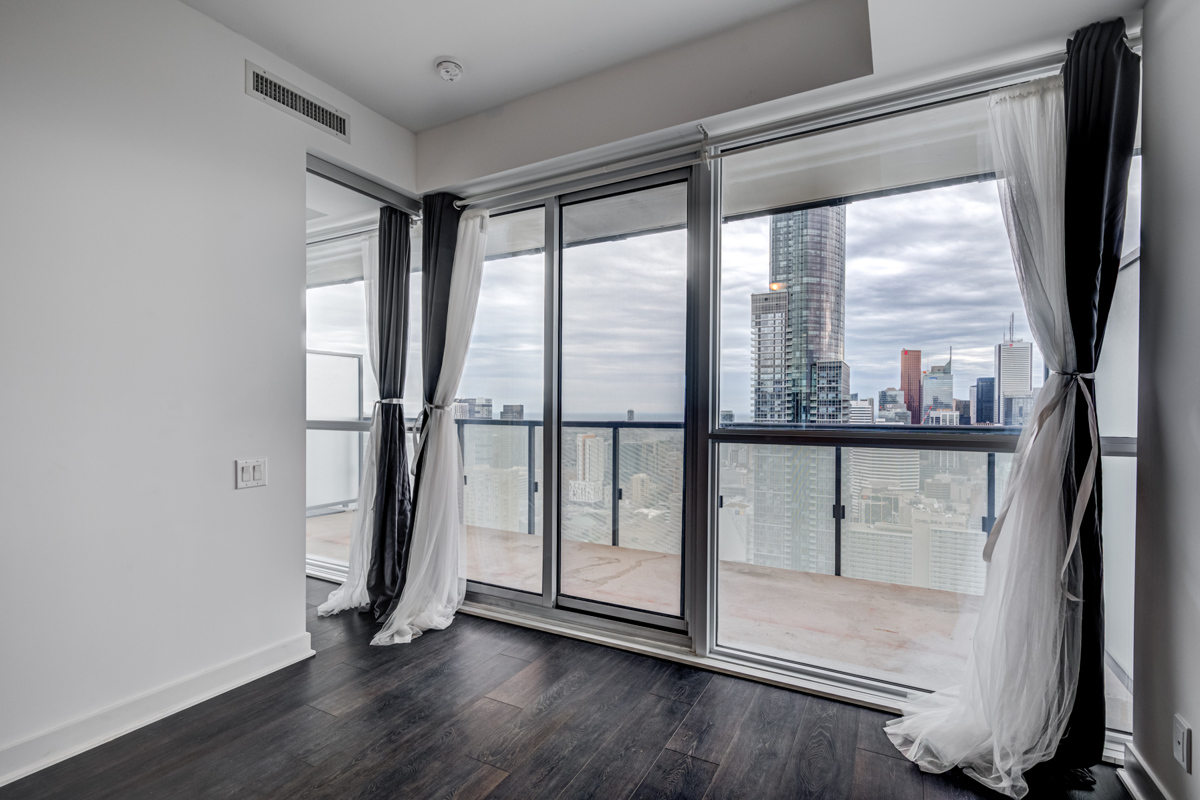 15 Grenville St living room and balcony with large windows offering view of Toronto.