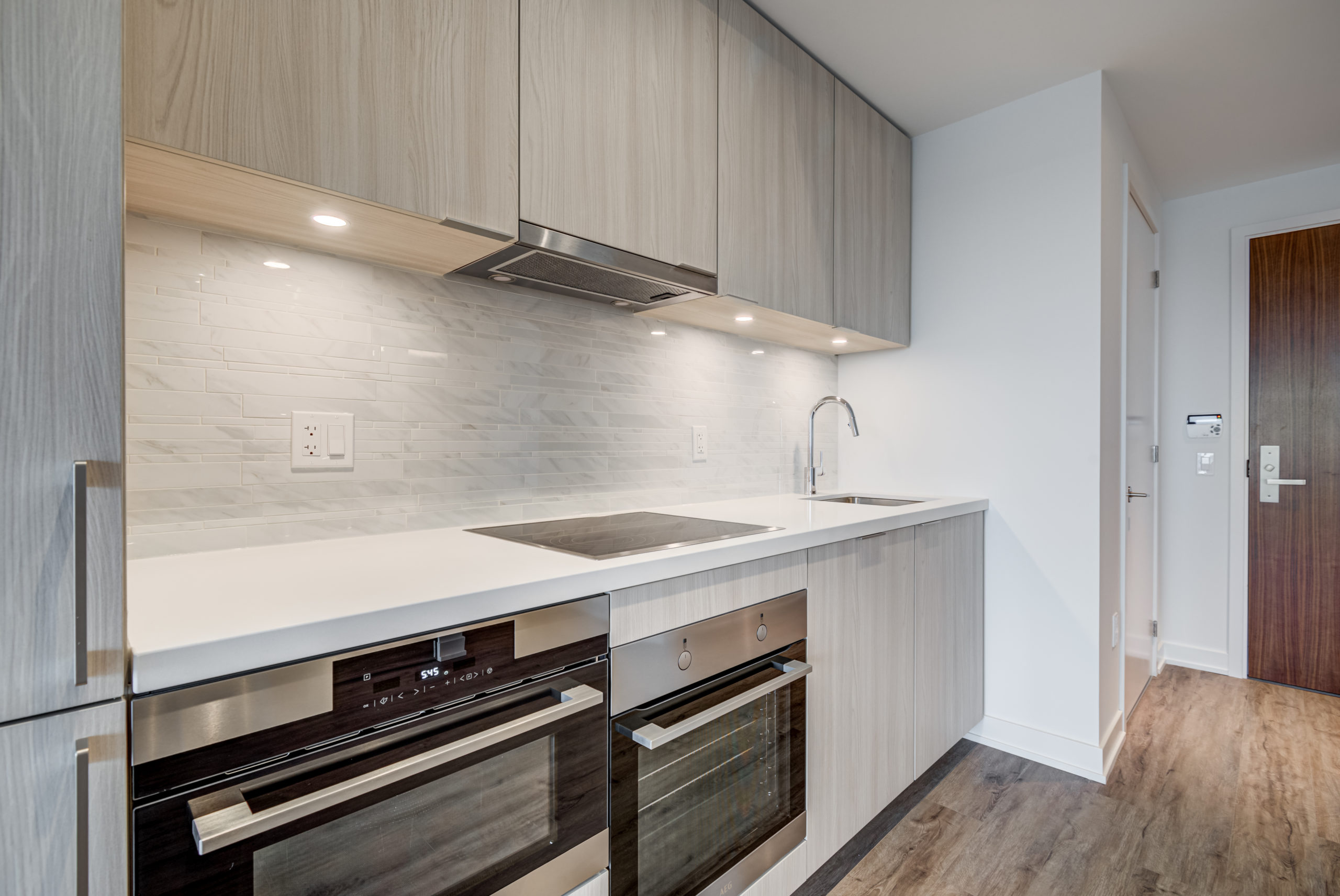 Condo kitchen with white counters, large cabinets with lights and glazed backsplash.