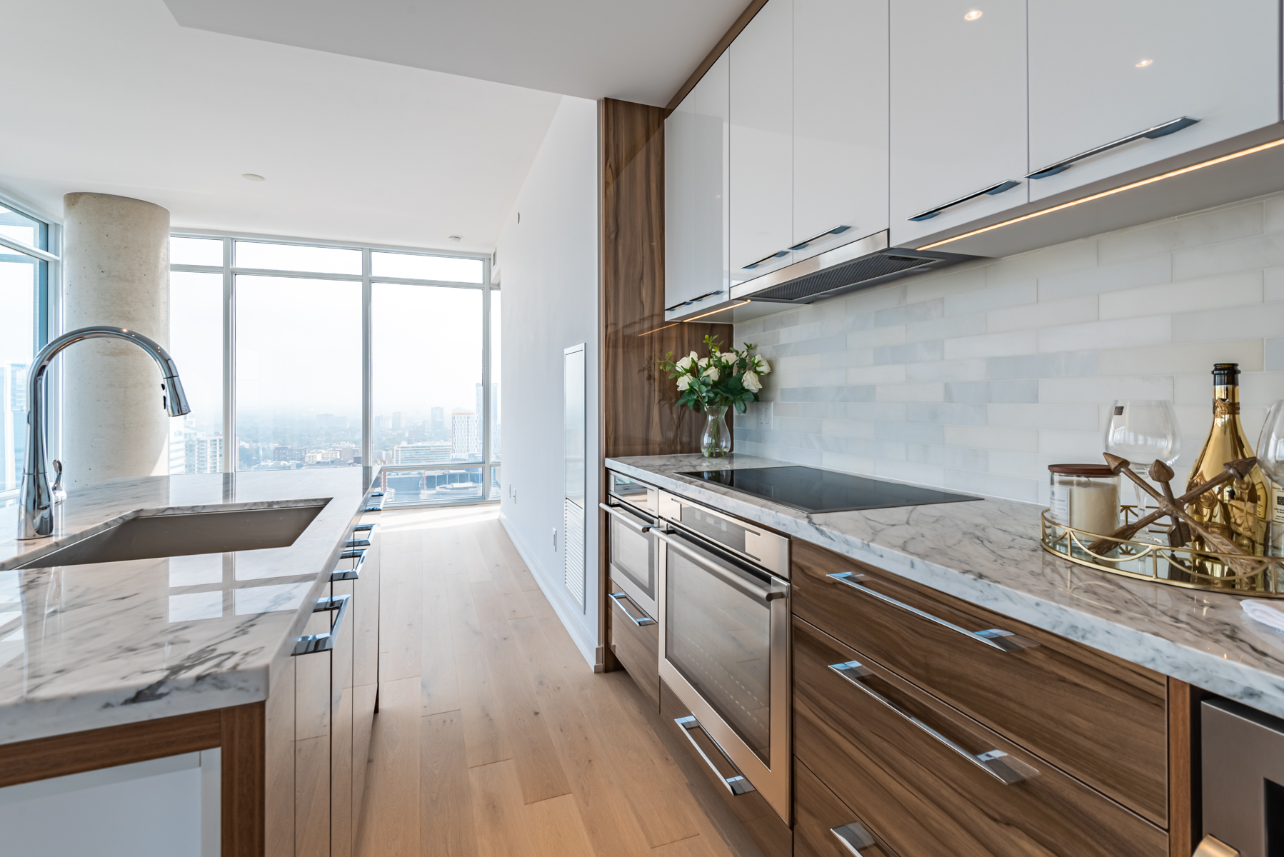 Condo kitchen with white marble counters, shiny cabinets and a tiled back-splash.