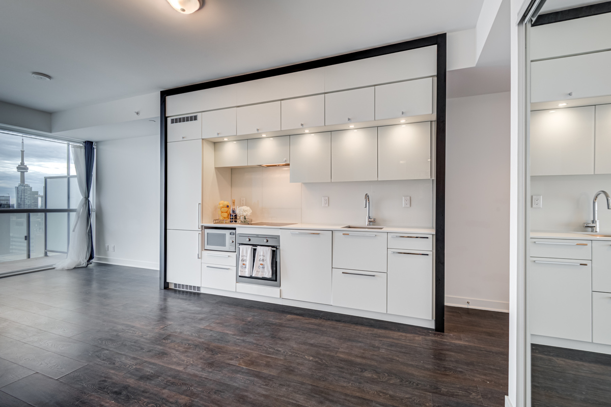Linear kitchen with shiny white cabinets.