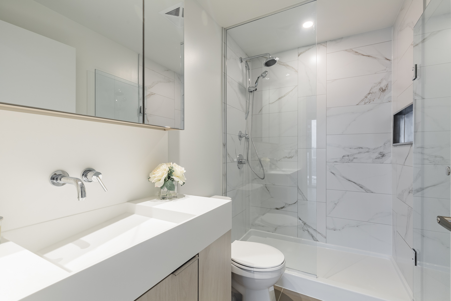 Beautiful ensuite bath with glass shower, vanity and marble tiles.