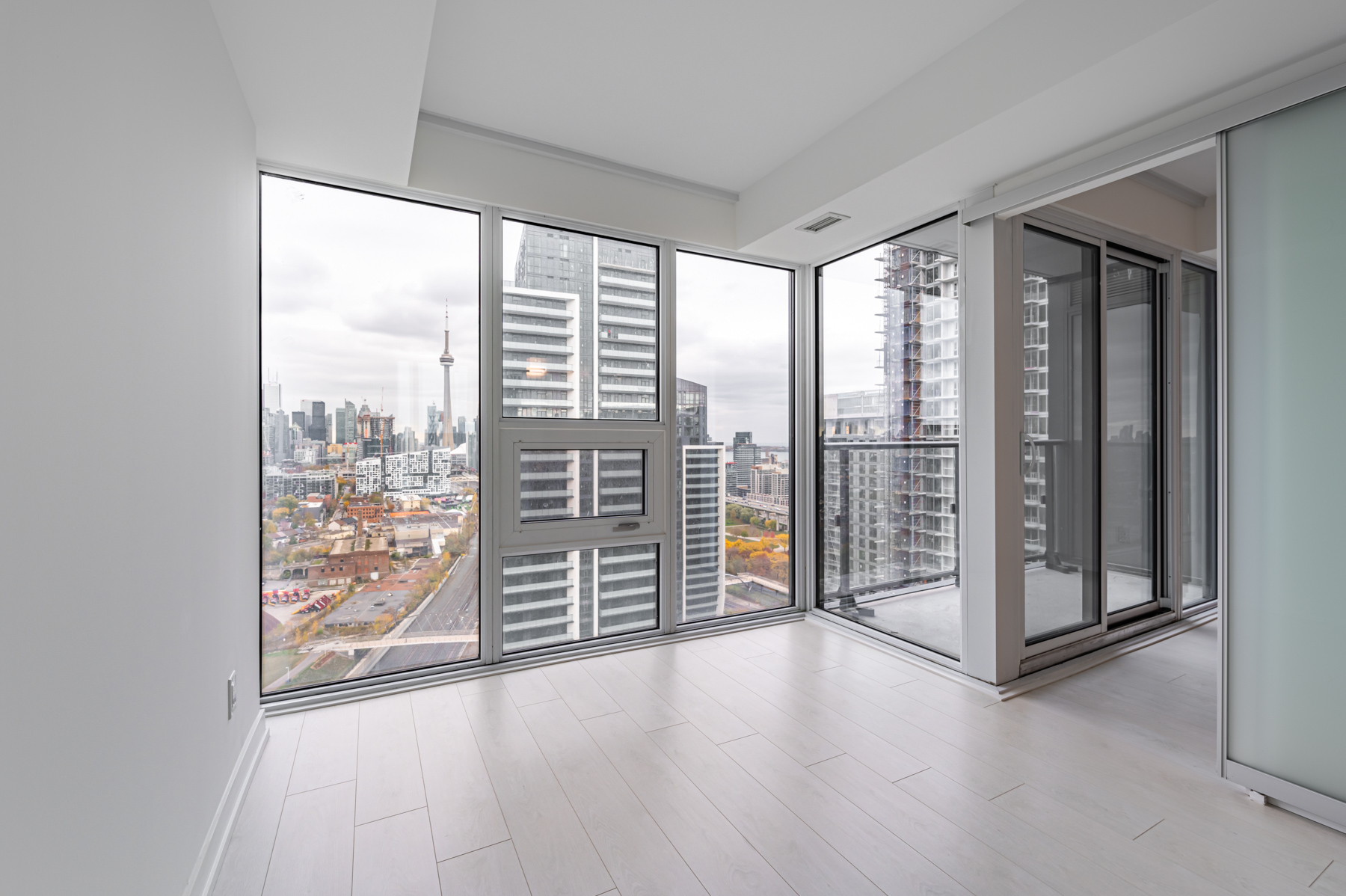 Empty condo bedroom with large glass windows showing Toronto.