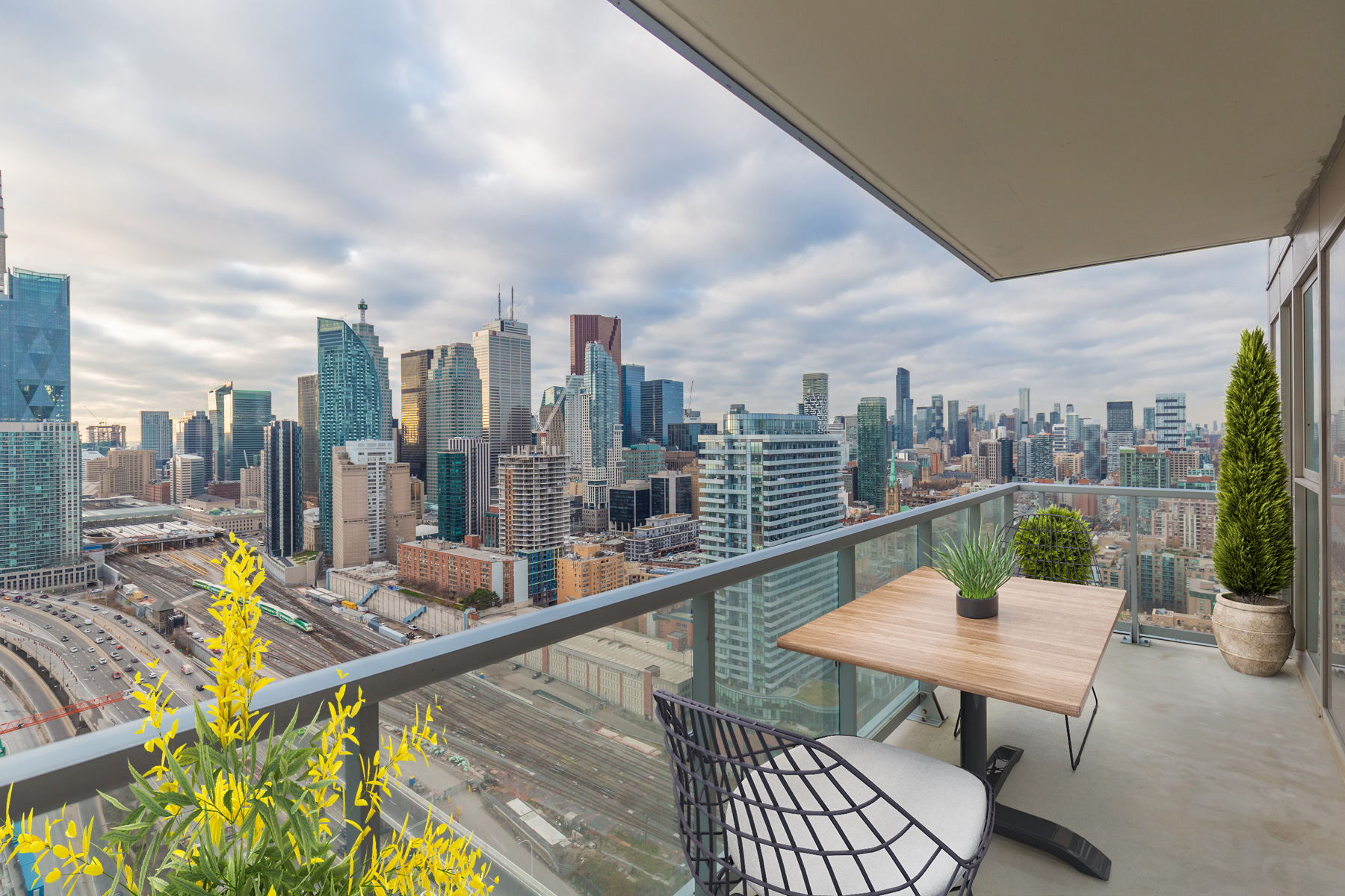 20 Richardson St balcony with glass panels and virtually staged patio furniture.