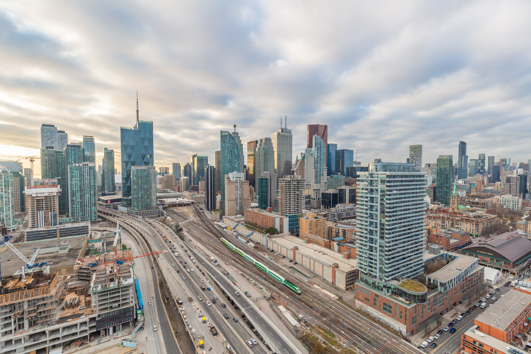 Toronto skyline with buildings, CN Tower needle, construction, highways and Go Train.