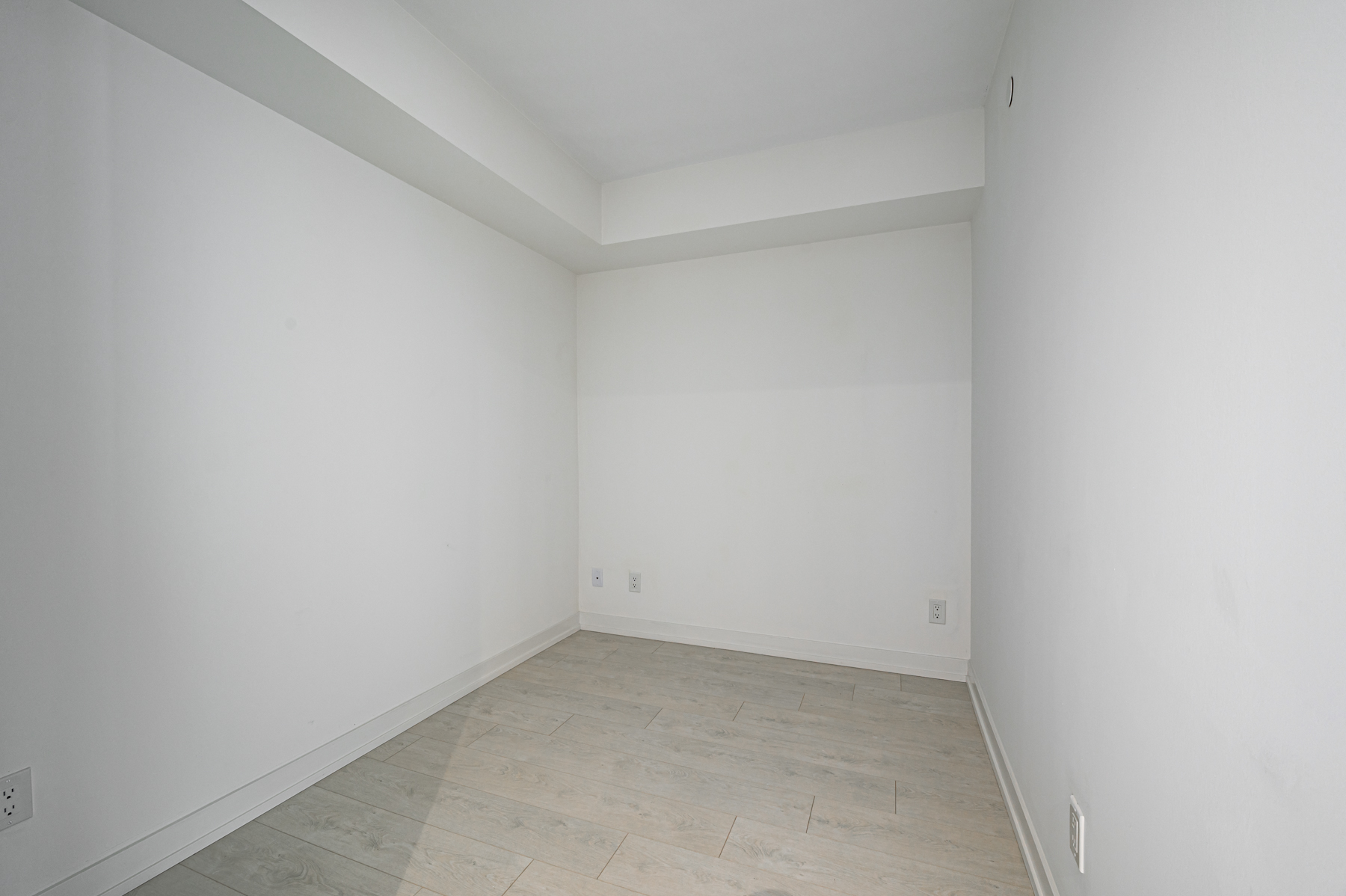 Empty condo den with gray walls and laminate floors.