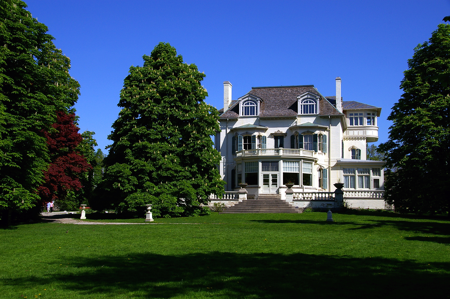 Spadina House in Toronto, a giant mansion with tall trees in foreground.