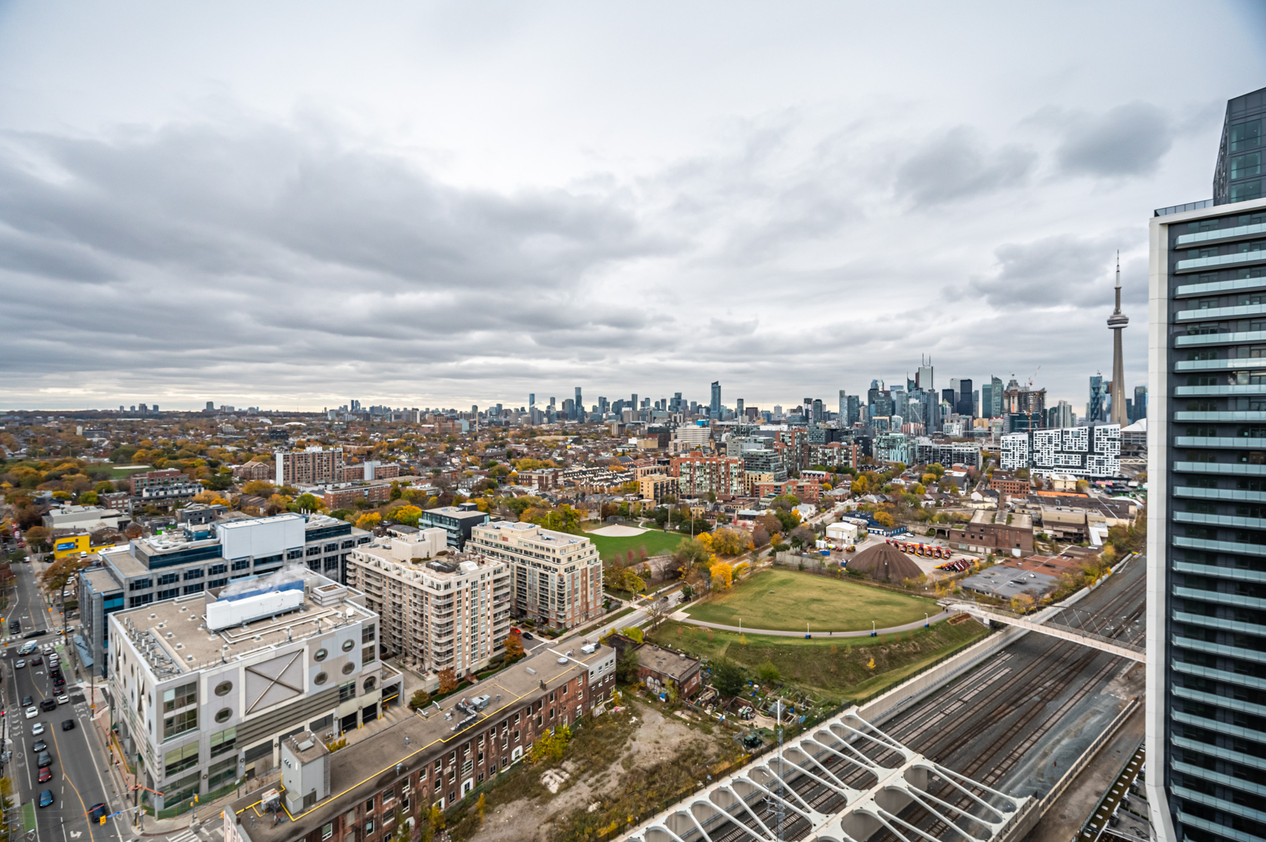 Balcony view of Toronto parks, railroads, buildings, bridges and CN Tower.