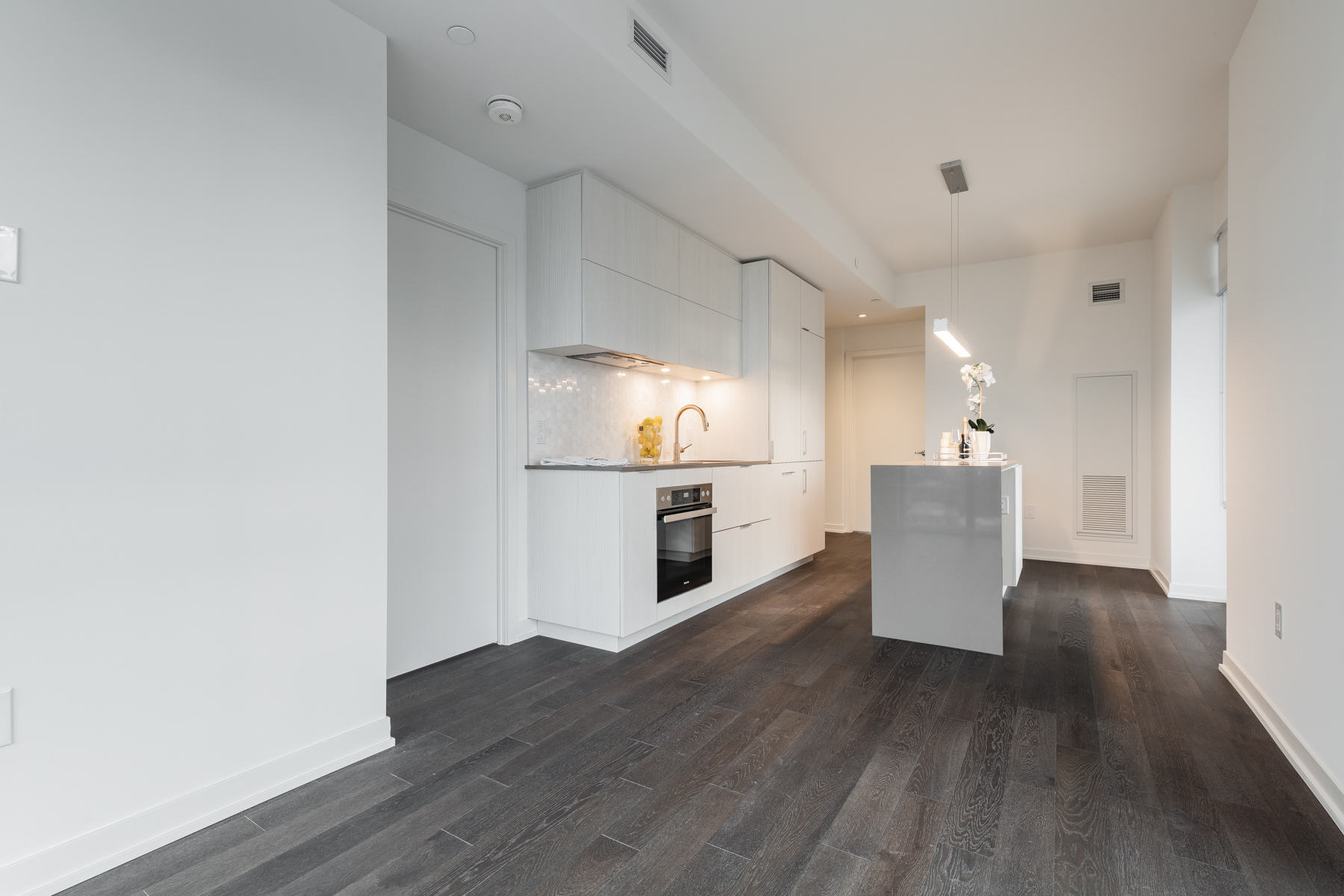 Dark hardwood floors and gray walls of 20 Richardson St dining room and kitchen.