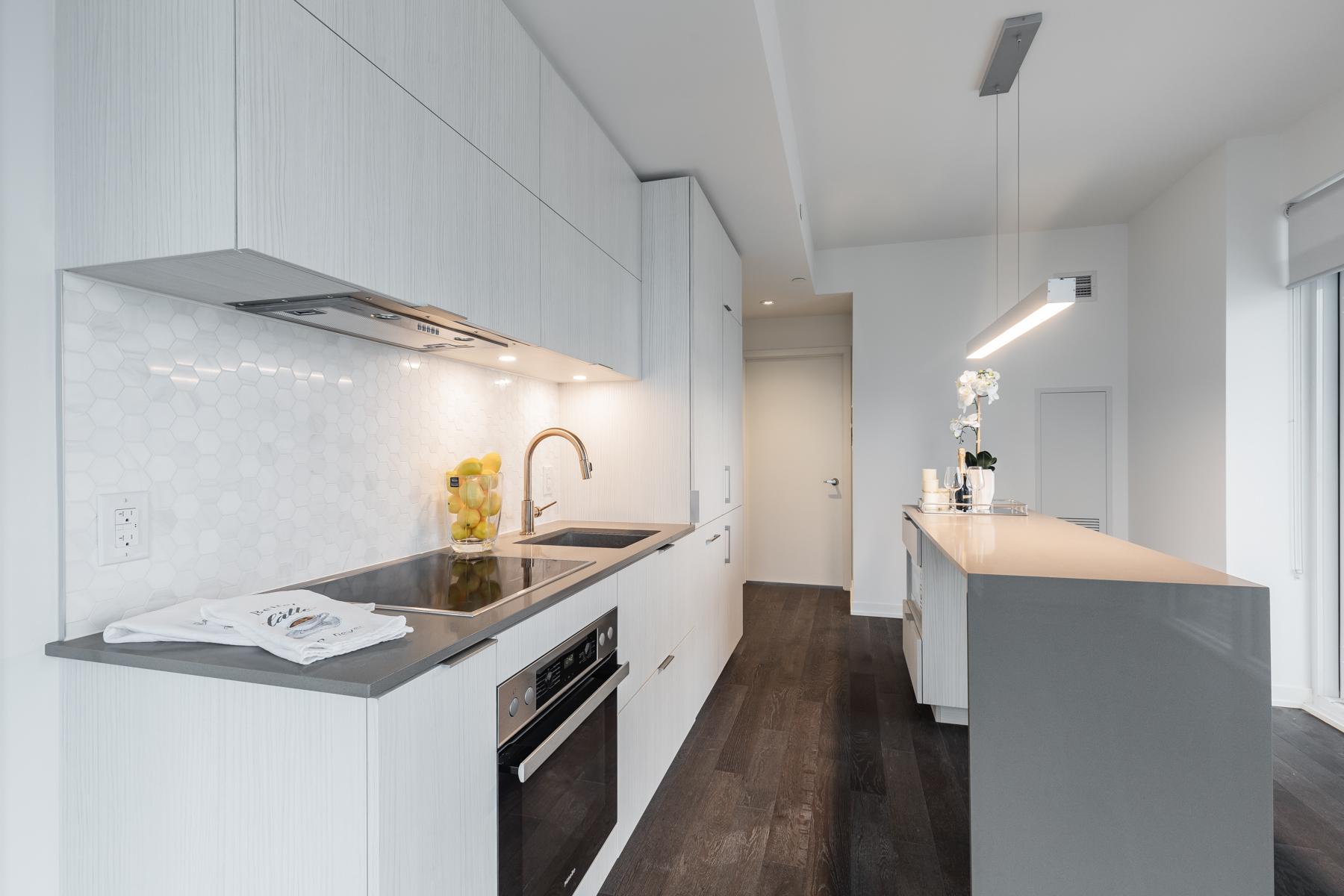 Close up of kitchen back-splash with shiny hexagon-shaped tiles.