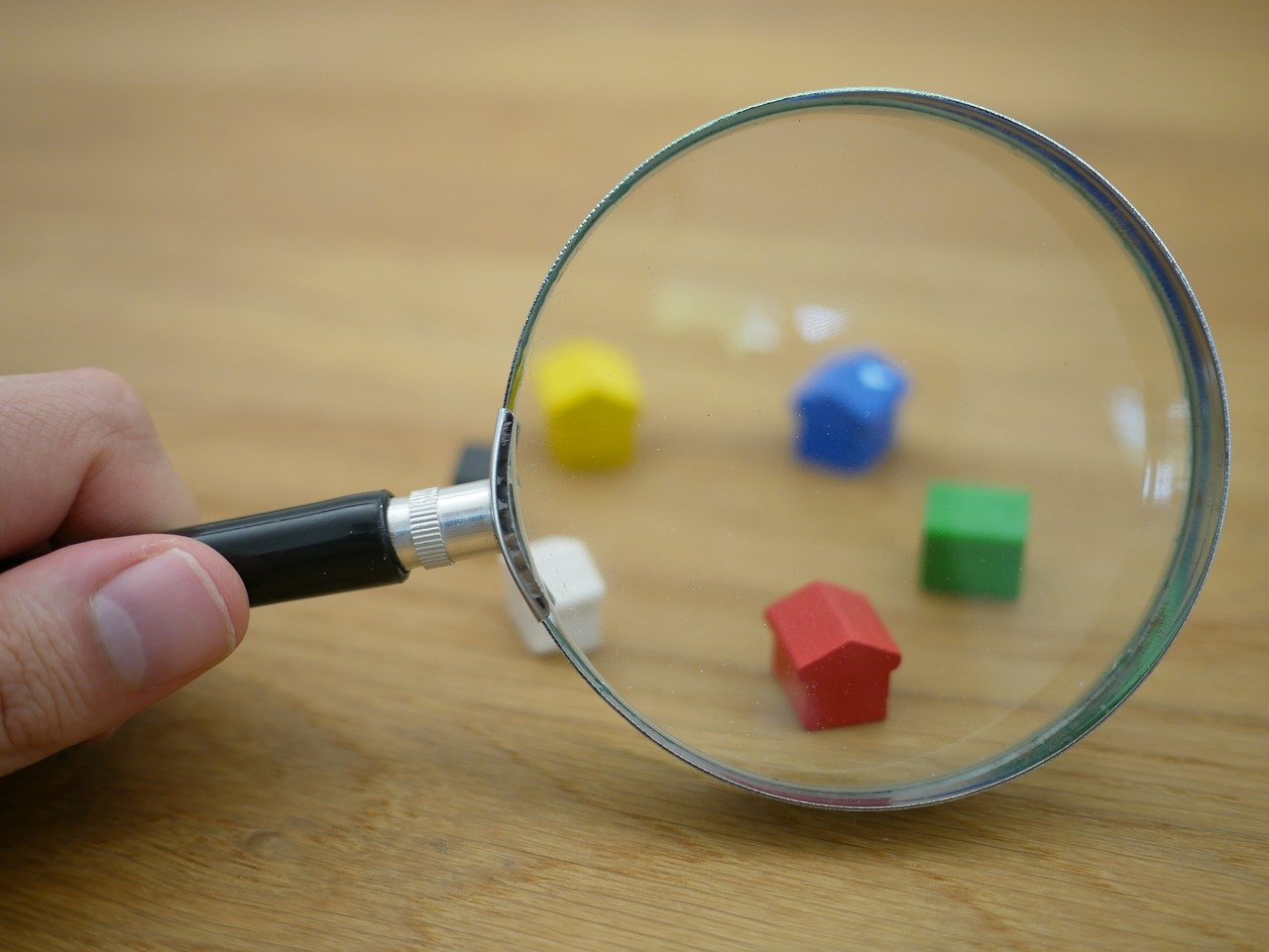 Hand holding magnifying glass in front of Monopoly house pieces.