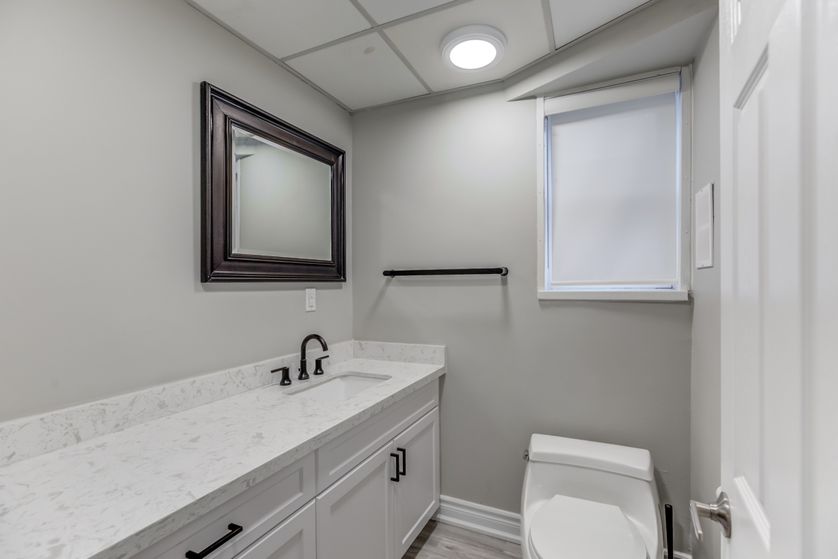 Powder room of 54 Huntington Ave with gray counters, storage cabinets and dark mirror.
