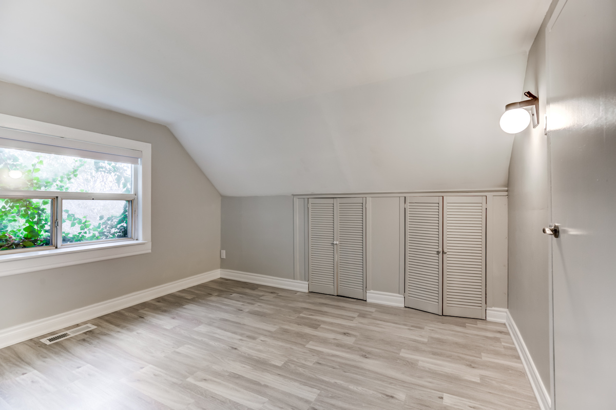 Empty master bedroom with two small closets.