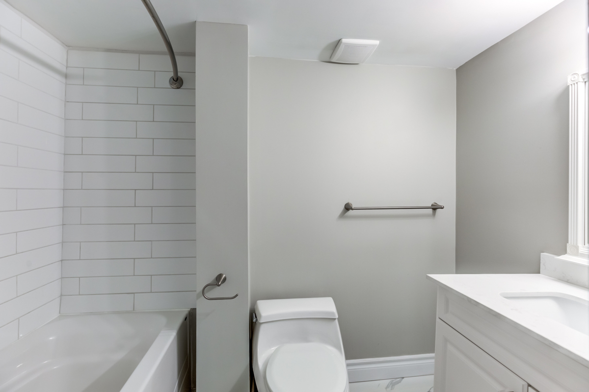 Bathroom with gray and white walls, bathtub and sink – 54 Huntington Ave.