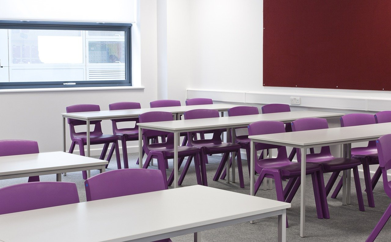 Empty classroom with white desk and purple chairs.