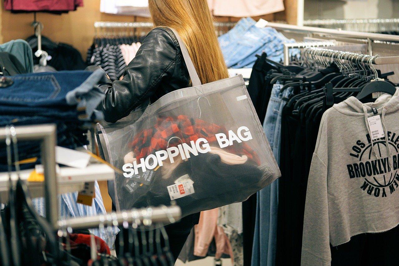 Young woman shopping among clothes racks.