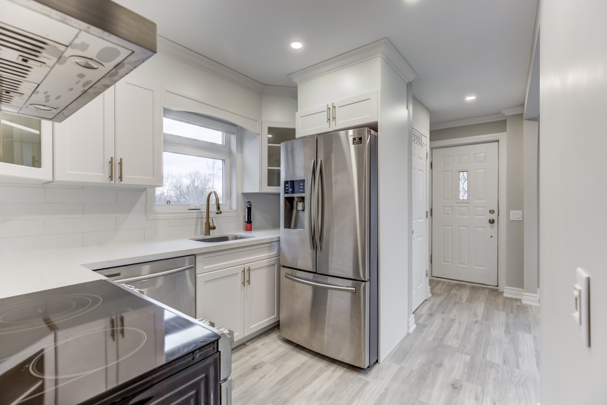 Renovated kitchen with white cabinets, tiled backsplash, laminate floors and pot-lights - 54 Huntington Ave.