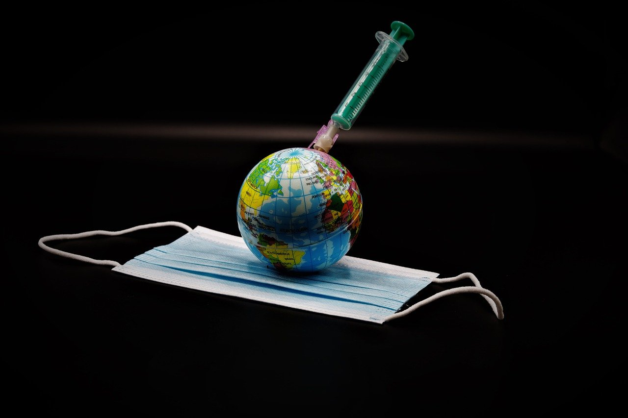 Planet Earth with needle and mask to show post-COVID world.
