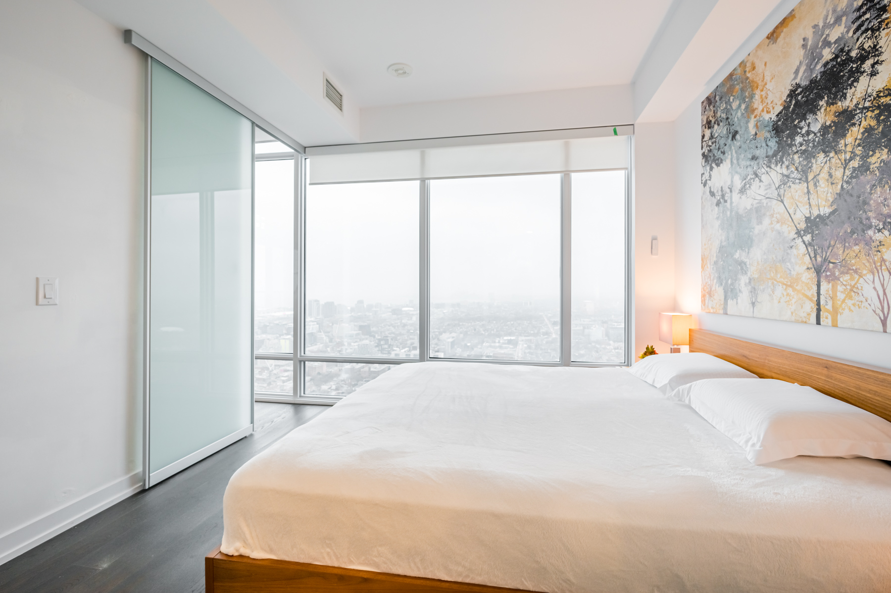 Large bedroom windows with electric blinds.