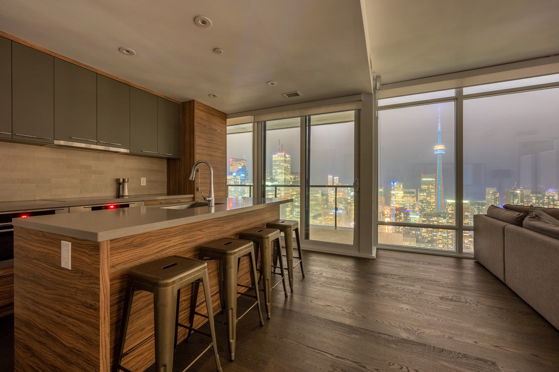 Condo dining room with view of Toronto at night.