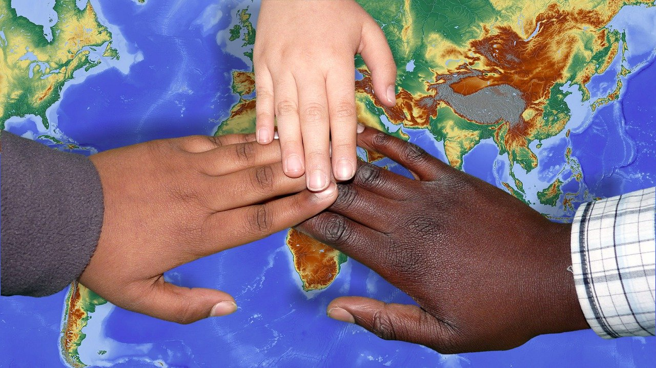 Close up of hands over map of earth showing immigration and importance of vaccines.