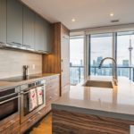 Condo kitchen and dining room with view of Toronto and CN Tower.