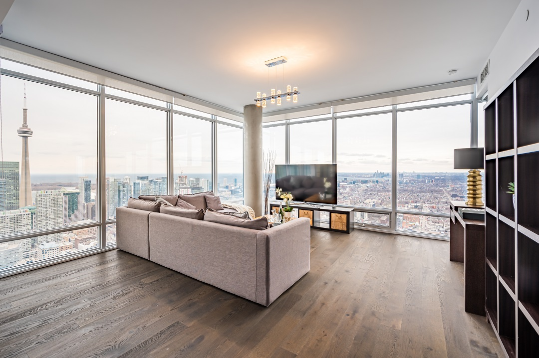 Condo living and dining room with hardwood floors, stylish lighting and floor-to-ceiling windows.
