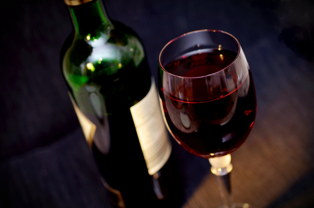 Close up of red wine in wine glass and green bottle.