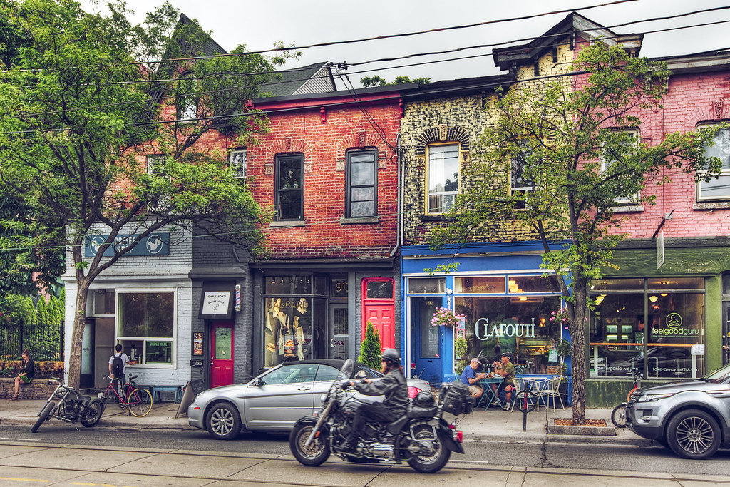 Across-the-street view of cafes and stores in Toronto's Trinity Bellwoods neighbourhood.