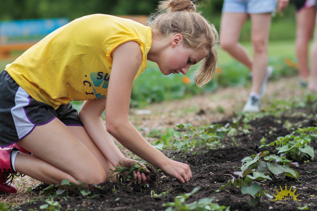 Teenage girl in yellow t-shirt gardening.