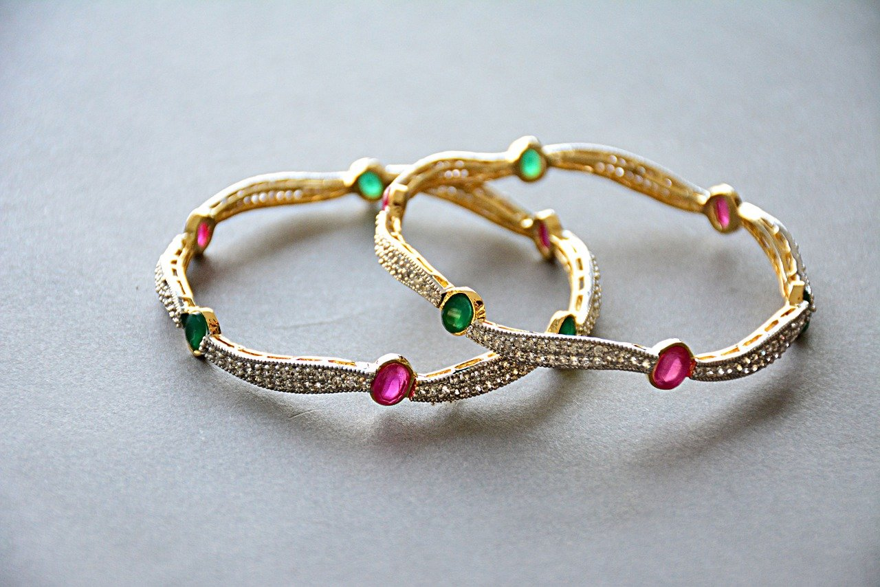 Pair of gold bracelets with pink and green gems.