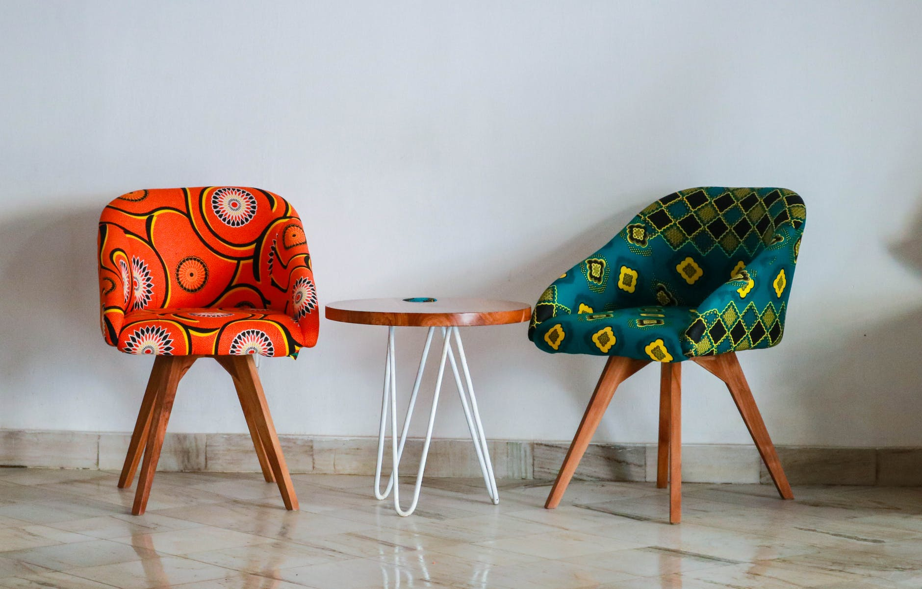 Two colourful chairs and round wooden table.