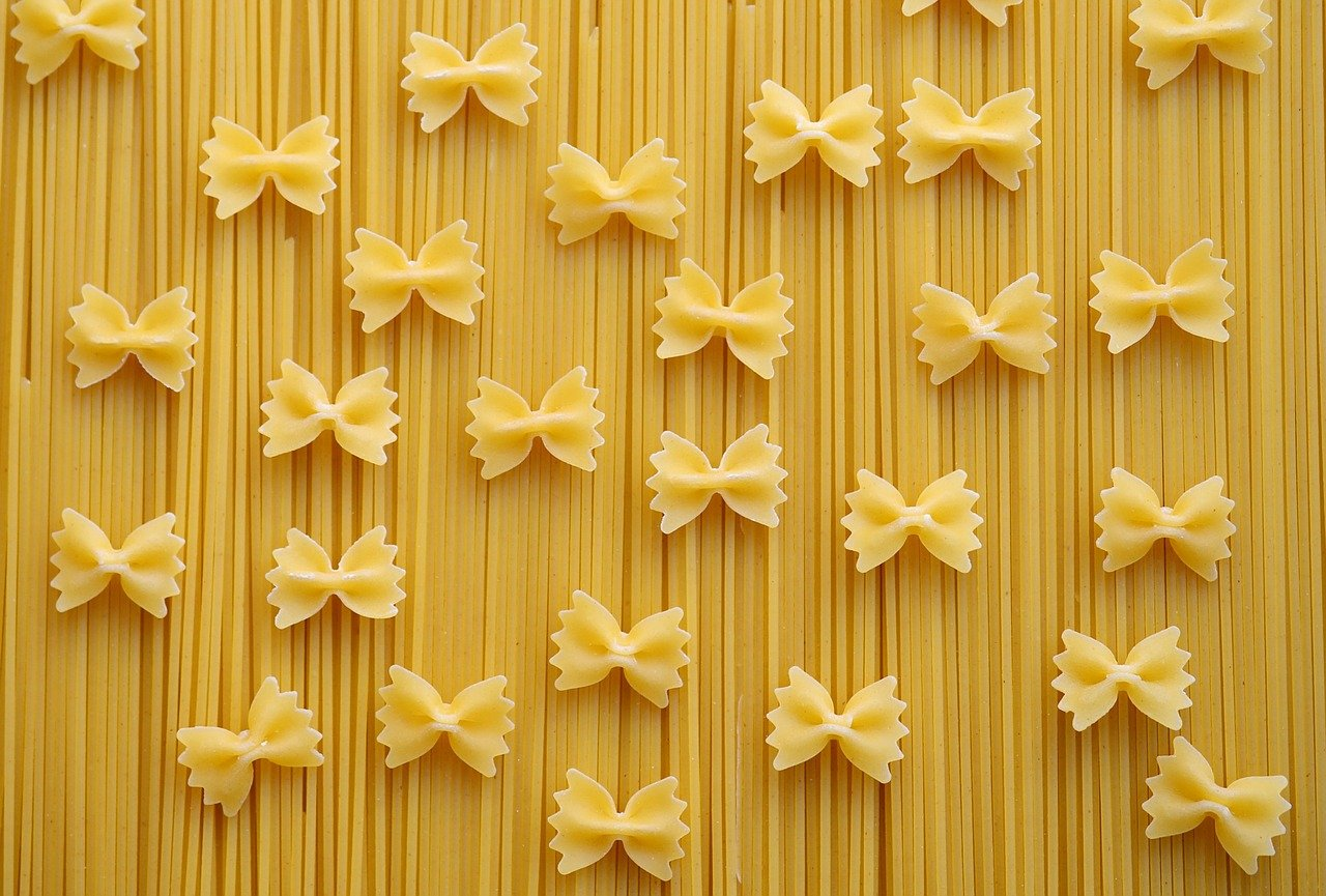 Uncooked bow-tie pasta and spaghetti.