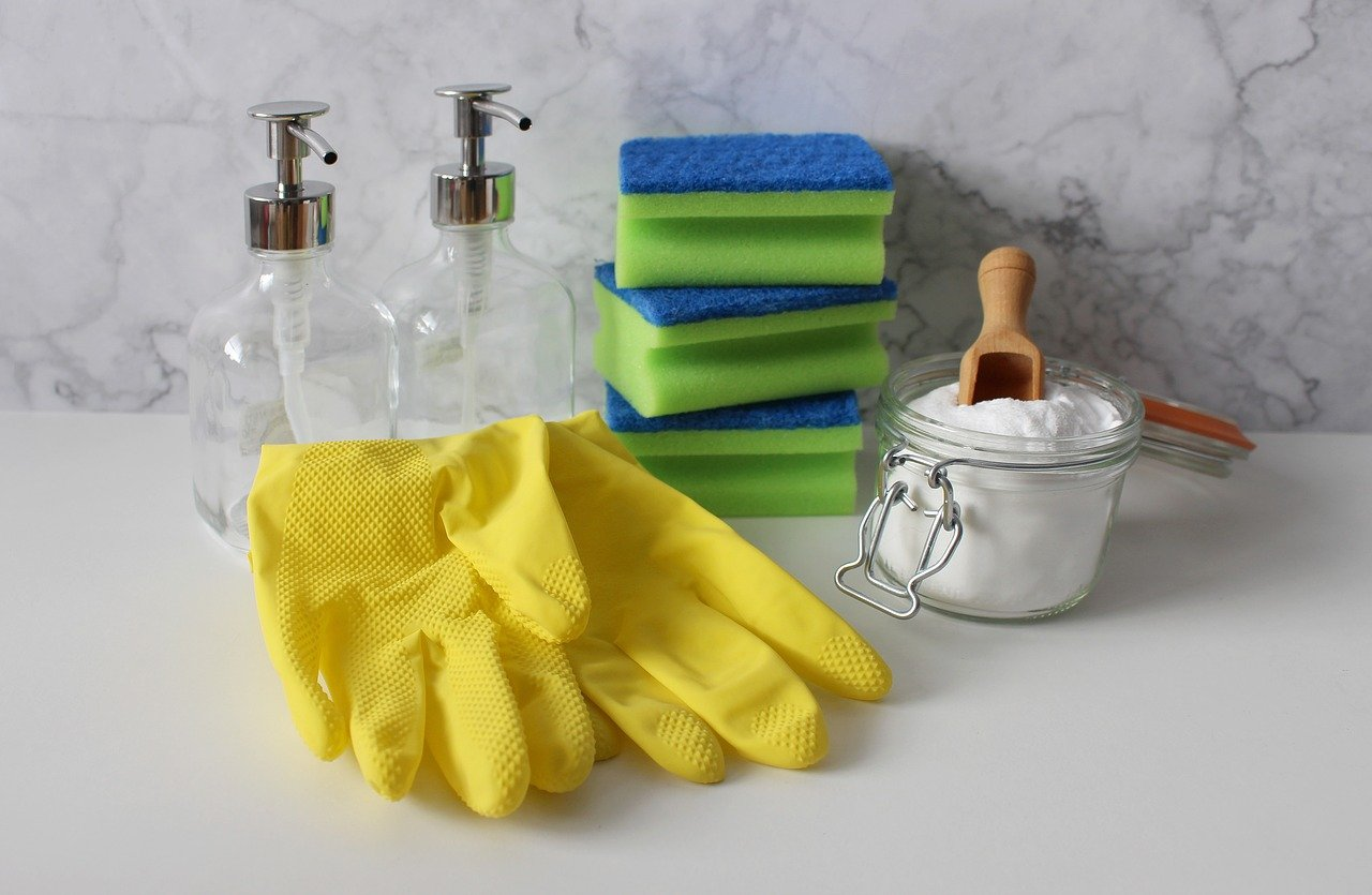 Close up of yellow gloves, sponges and cleaning supplies.