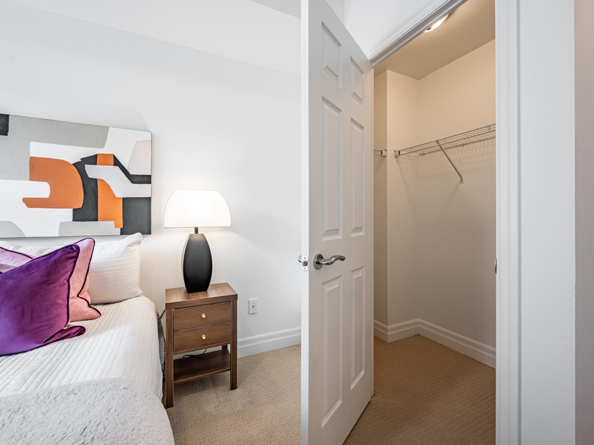 Condo bedroom with walk-in closet with its door open.